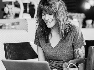 עיצוב- בחורה שיושבת עם מחשב נייד ונראית מאושרת
