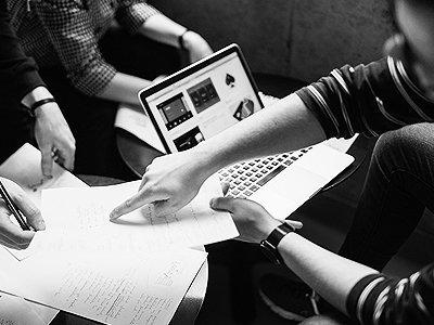 תמונה לצורך עיצוב, אנשים יושבים בשולחן ועובדים עם מחשב נייד וניירת